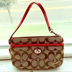 Coach wristlet with classic design & coral accents
